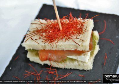 Sandwich de guacamole, salmón y queso fresco, cubierto con hilos de chili