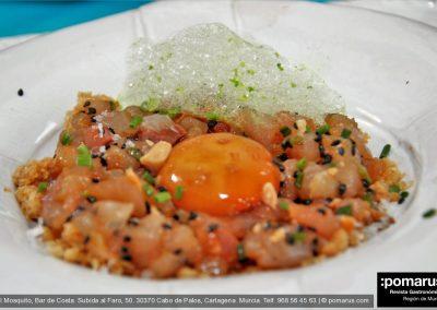 Tartar de hijada de lecha con yema de huevo en soja, tomate y crocante de almendra